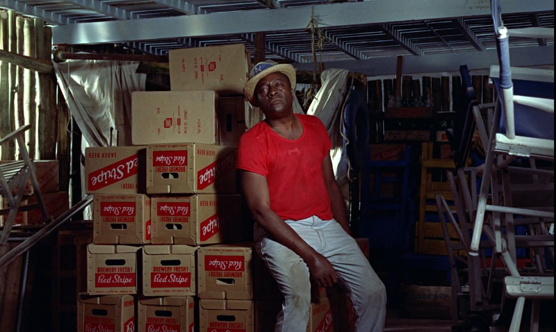 Boxes of Jamaica's signature Red Stripe beer surround Quarrel in Dr. No (1962)