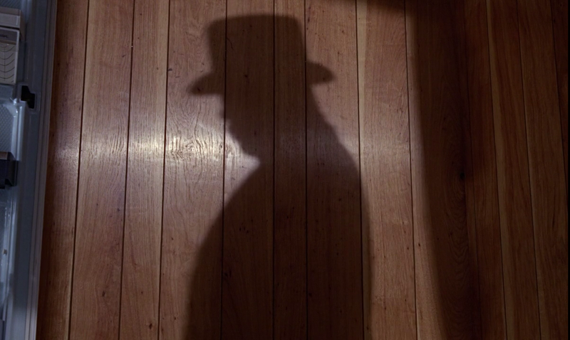 Shadow of Oddjob over some tacky wood paneling, , played by Harold Sakata, in Goldfinger (1964)