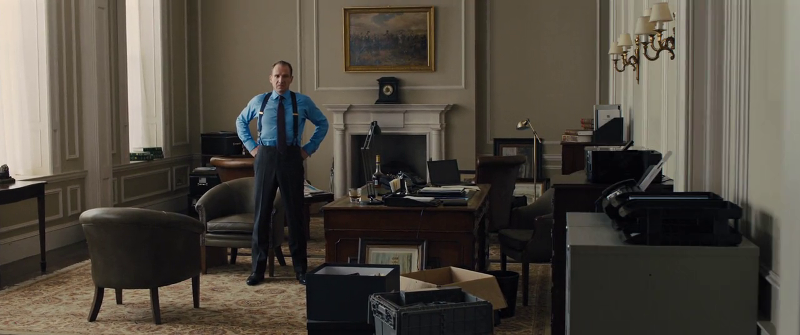 Gareth Mallory (played by Ralph Fiennes) stands awkwardly after M leaves his office in Skyfall (2012)