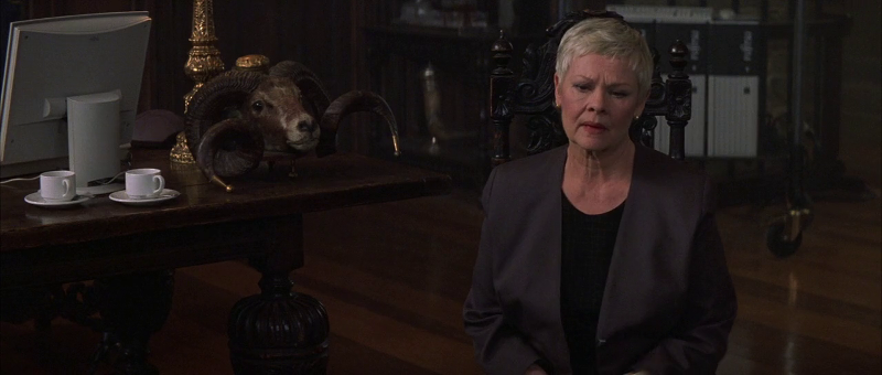 Judi Dench as M in The World Is Not Enough (1999), with the ram head