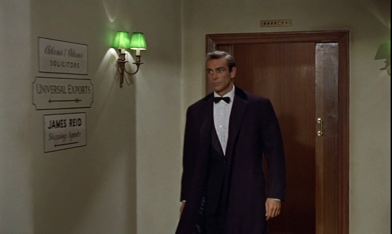 007 is shown walking into M's office, which has a Universal Exports sign on the outside
