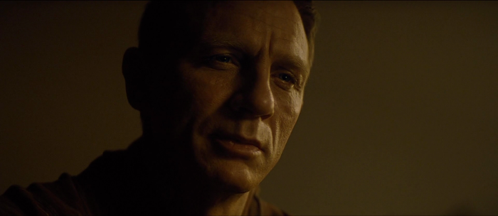 James Bond (Daniel Craig) cracks a smile of nostalgia looking at his old family photo in Spectre (2015)