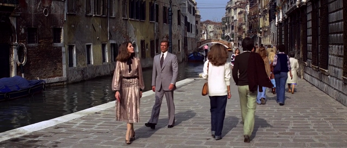 Holly Goodhead (Lois Chiles) and James Bond (Roger Moore) walk down a Venice street in Moonraker (1979) - 007 obviously embarrassed by her dress choice
