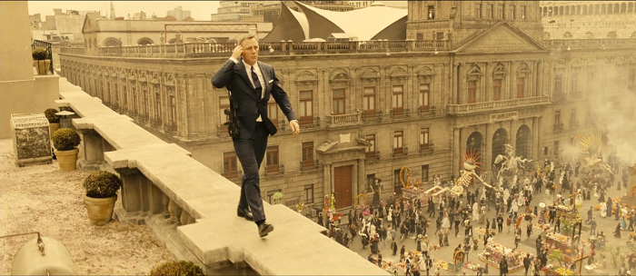 James Bond (Daniel Craig) casually walks high above the Day of the Dead parade in the opening sequence of Spectre (2015)