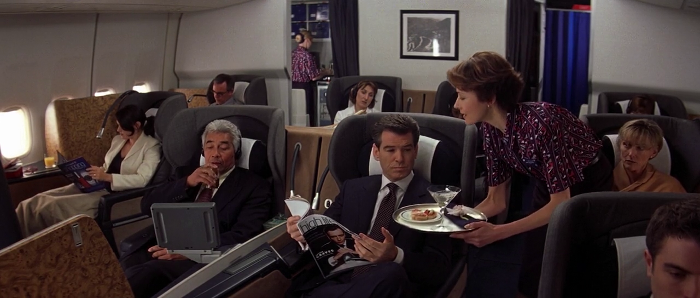 James Bond (Pierce Brosnan) is served a vodka martini by a flight attendant (Sir Roger Moore's daughter Deborah Moore) in Die Another Day (2002)